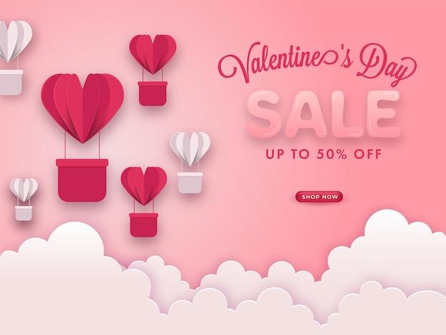 Cartel de venta del día de san valentín con oferta de descuento, globos de aire caliente cortados en papel y nubes sobre fondo rosa pastel.