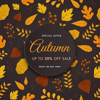 Cartel de venta de otoño, ramas de bayas y varias hojas decoradas sobre fondo marrón oscuro.