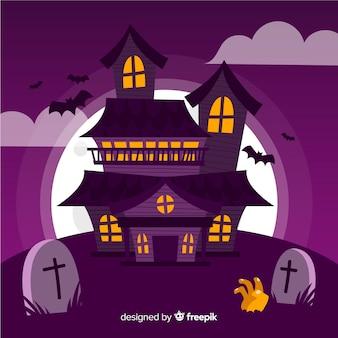 Casa de halloween en un cementerio y mano zombie