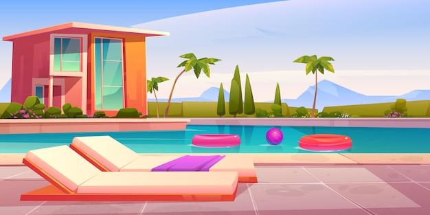 Casa y piscina con tumbonas.