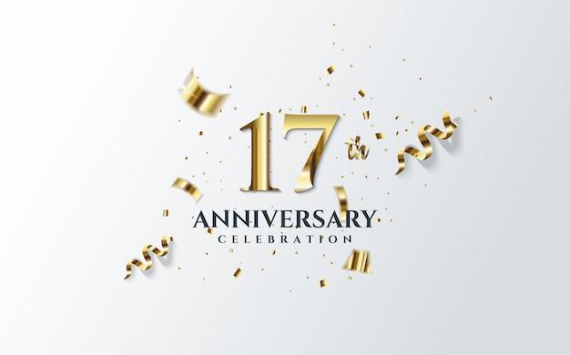 Celebración del aniversario con la ilustración del número 17 en oro y pedazos dispersos de papel dorado.