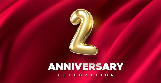 Celebración del primer aniversario. número de oro 2 sobre fondo textil drapeado rojo.