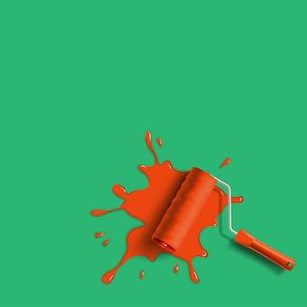 Cepillo de rodillo con salpicaduras de pintura roja en la pared verde