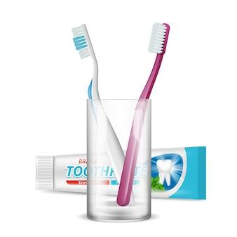 Cepillos de dientes en vaso y pasta de dientes