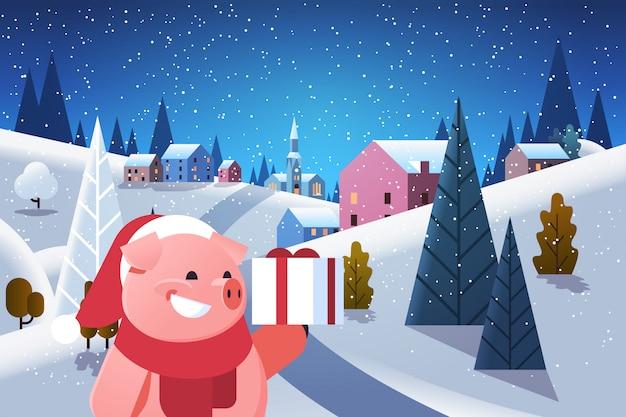 Cerdo mantenga caja de regalo presente durante la noche invierno aldea casas montañas colinas paisaje nevadas