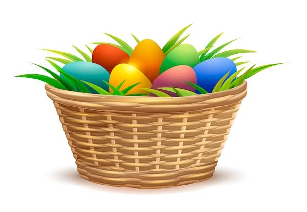Cesta de mimbre llena de huevos de pascua en pasto