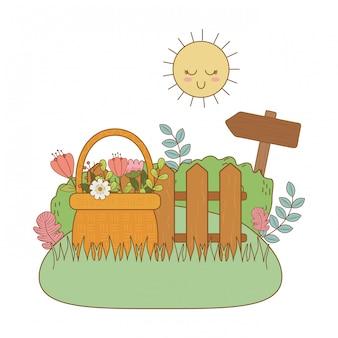 Cesta de paja con flores y valla en jardín.