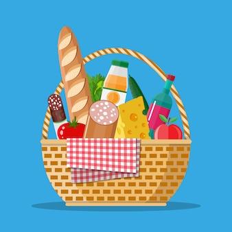 Cesta de picnic wicker llena de productos.