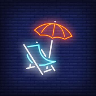 Chaise-lounge, letrero de neón. silla de playa y paraguas en fondo oscuro de la pared de ladrillo.