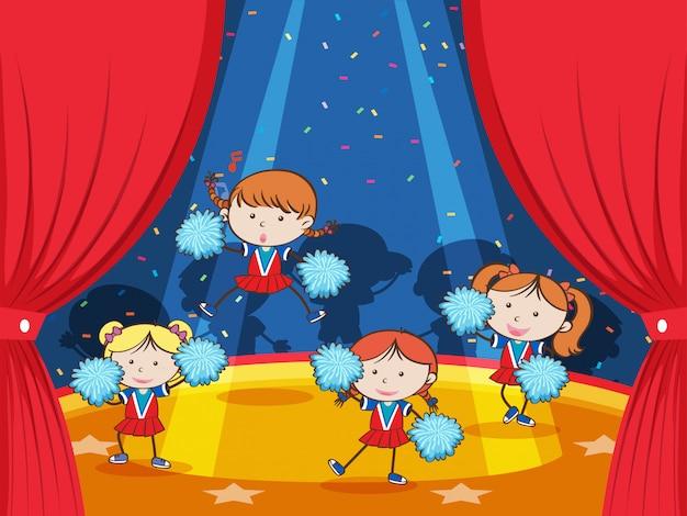 Cheerleader team en el escenario bajo limelight