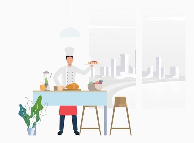 Chef cocinando la cena en la mesa de la cocina y sosteniendo el pastel