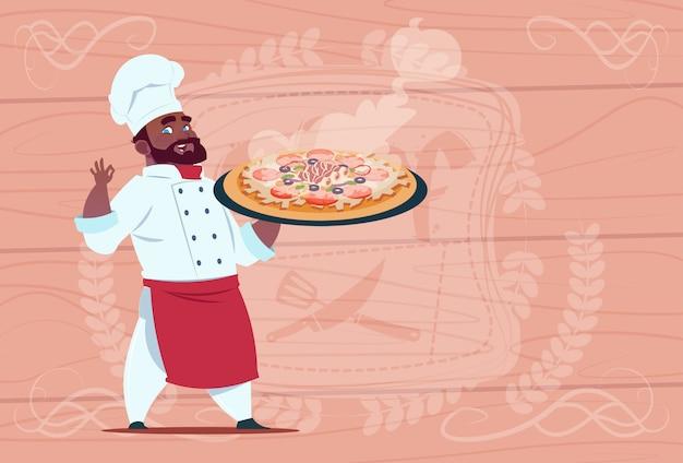 Chef cocinero afroamericano holding pizza sonriendo jefe de dibujos animados en restaurante blanco uniforme sobre fondo con textura de madera