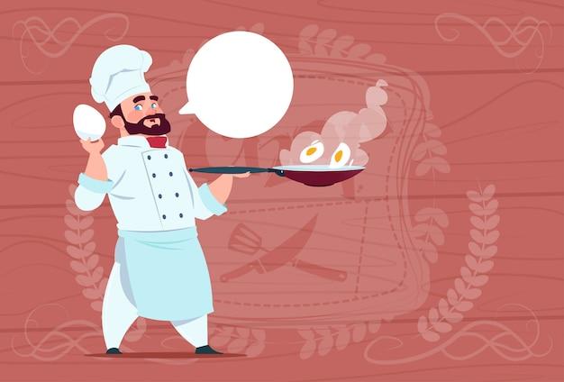 Chef cocinero sosteniendo una sartén con huevos sonriendo jefe de dibujos animados en restaurante blanco uniforme sobre fondo de textura de madera