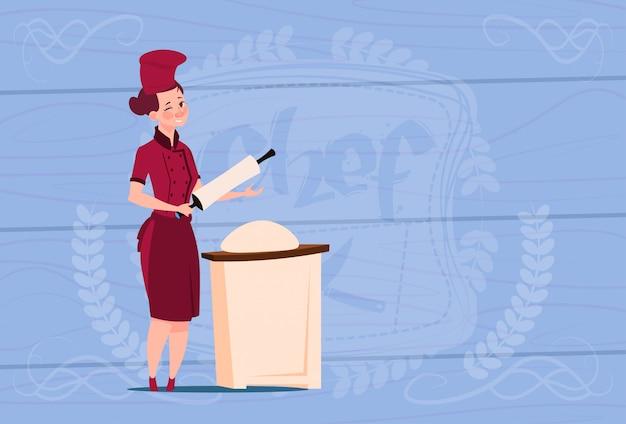 Chef mujer chef trabajando con masa jefe de dibujos animados en restaurante uniforme sobre fondo con textura de madera
