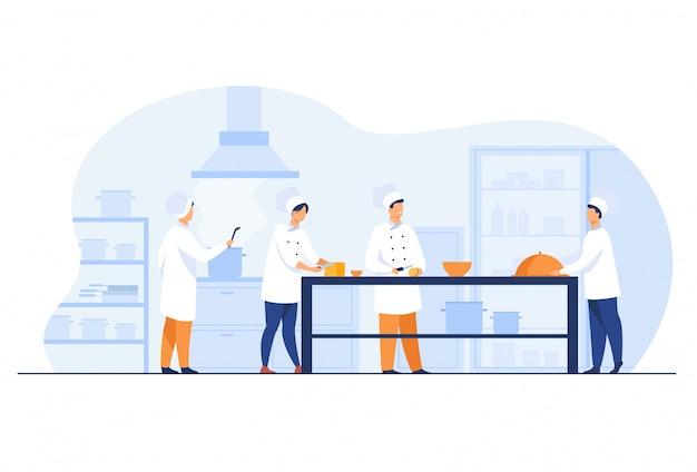 Chefs, cocineros y camareros que trabajan en la cocina del restaurante.