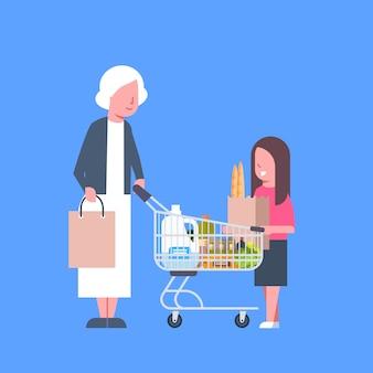 Chica con la abuela de compras con bolsa de papel y carro lleno de productos comestibles