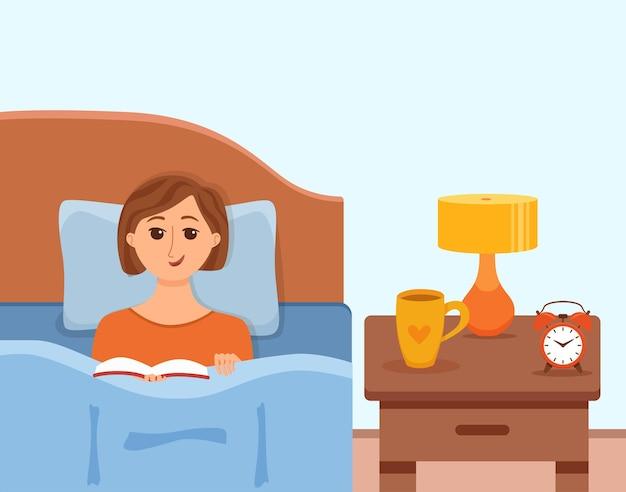 Chica acostada en la cama en el dormitorio de casa y leyendo un libro en sus manos bajo la luz de la lámpara