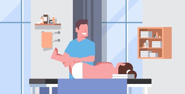 Chica acostada en la mesa de masaje masajista profesional terapeuta haciendo tratamiento curativo masajear paciente tratar piernas manual fisioterapia concepto clínica médica gabinete interior horizontal