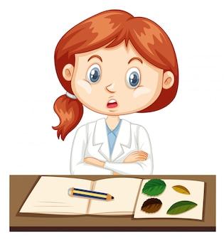 Chica en bata de laboratorio registrando datos de experimentos en el cuaderno