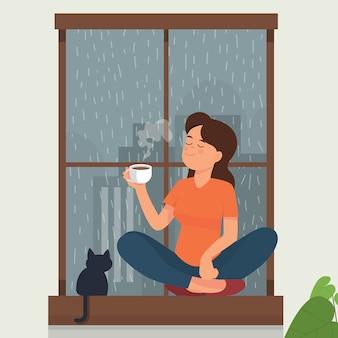 Chica bebe té / café cerca de la ventana mientras llueve afuera