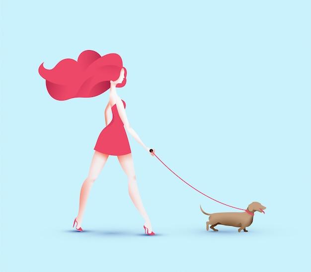 Chica bonita pelirroja caminando con perro salchicha