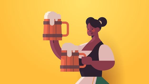 Chica camarera sosteniendo jarras de cerveza oktoberfest concepto de celebración de fiestas afroamericana en ropa tradicional alemana divirtiéndose