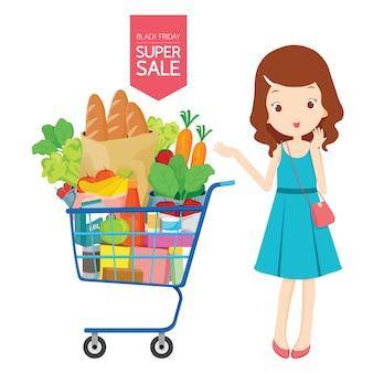 Chica con carrito de compras lleno de comida, comida, bebida y vegetales