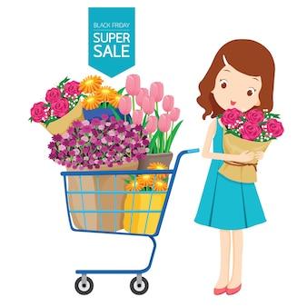 Chica y carrito de compras lleno de flores