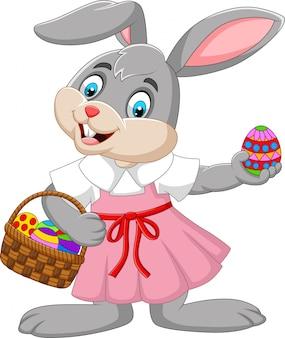 Chica de conejito de pascua de dibujos animados con una canasta de huevo