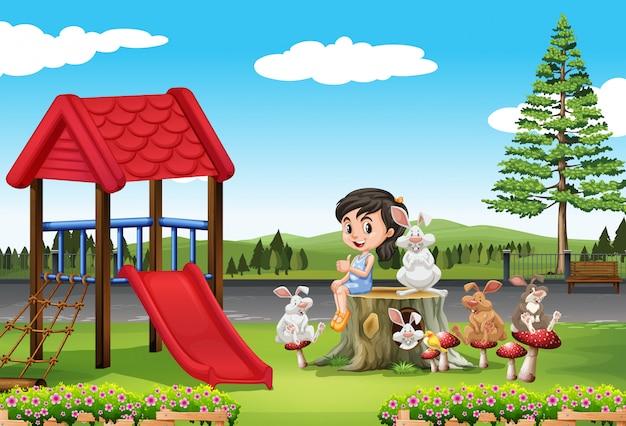 Chica y conejos en el patio de recreo.