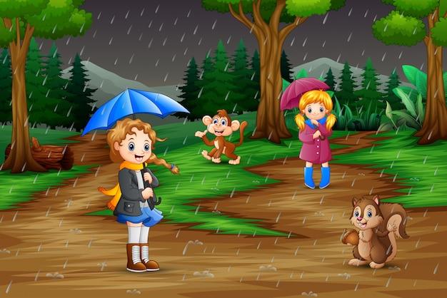 Chica de dibujos animados dos jugando con animales bajo la lluvia