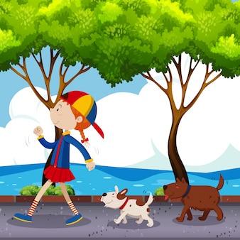 Chica y dos perros caminando en la calle
