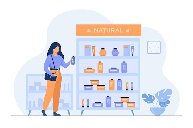 Chica eligiendo productos de belleza ecológica en la tienda de cosméticos, de pie en el estuche con cremas y lociones y tomando la botella de champú.