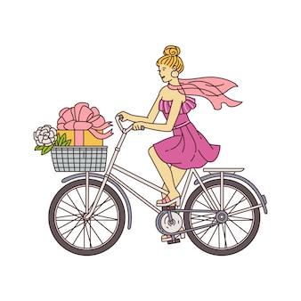 Chica femenina en vestido rosa montando una bicicleta con caja de regalo en la cesta delantera - elegante mujer de dibujos animados sentada en bicicleta retro que va a la fiesta.