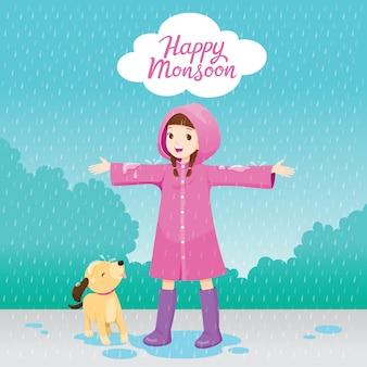 Chica en impermeable rosa estira los brazos felizmente bajo la lluvia con su perro, feliz monzón