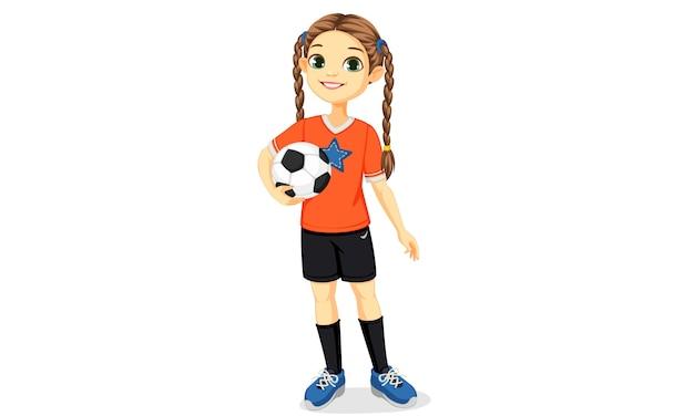 Chica joven jugador de fútbol en pose de pie sosteniendo una ilustración de balón de fútbol