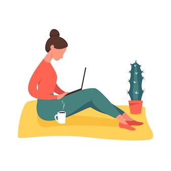 Chica joven que se sienta en el suelo con la computadora portátil