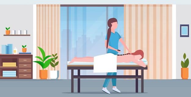 Chica con masaje de espalda con piedras calientes masajista en masaje uniforme cuerpo paciente mujer acostada en la cama tratamientos concepto lujo spa salón clínica gabinete interior longitud completa horizontal