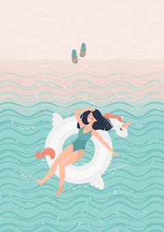 Chica morena en traje de baño verde en una ilustración de unicornio de goma blanca