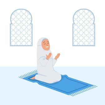 Chica musulmana sentarse y rezar en estera de oración