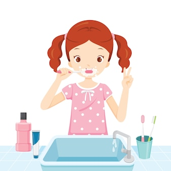 Chica en pijama cepillándose los dientes en el baño.