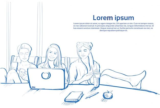 Chica de tres bocetos sentados juntos usando una computadora portátil y chateando en teléfonos inteligentes de células