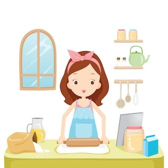 Chica trillar harina con tablet en cocina