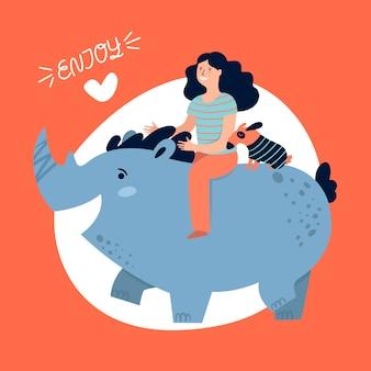 Chica viaja y disfruta montando un rinoceronte.