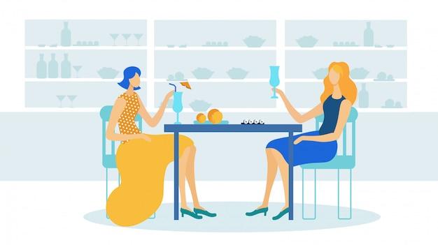 Chicas bebiendo cócteles en la cafetería o restaurante.