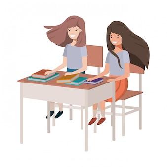 Chicas jóvenes estudiantes sentados en el escritorio de la escuela