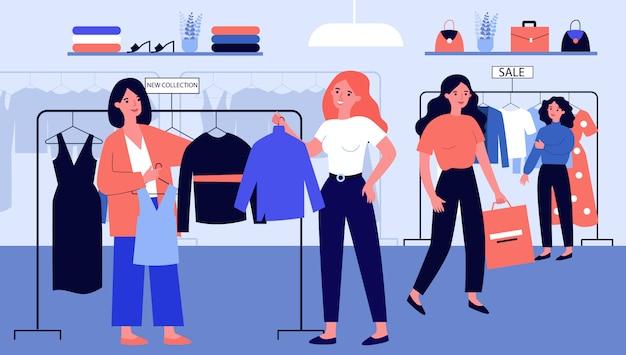 Chicas en la tienda de moda moderna eligiendo ropa en percha