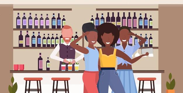 Chicas tomando fotos selfie en la cámara del teléfono inteligente personas relajándose en el bar bebiendo cócteles barman sirviendo a los clientes moderno café interior retrato horizontal