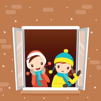 Chicas en la ventana, nieve cayendo, temporada de invierno