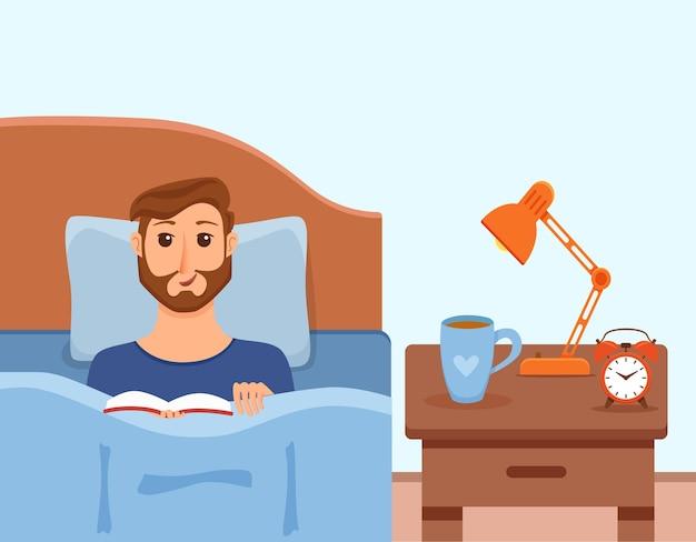 Chico acostado en la cama en el dormitorio de su casa y leyendo un libro en sus manos bajo la luz de la lámpara